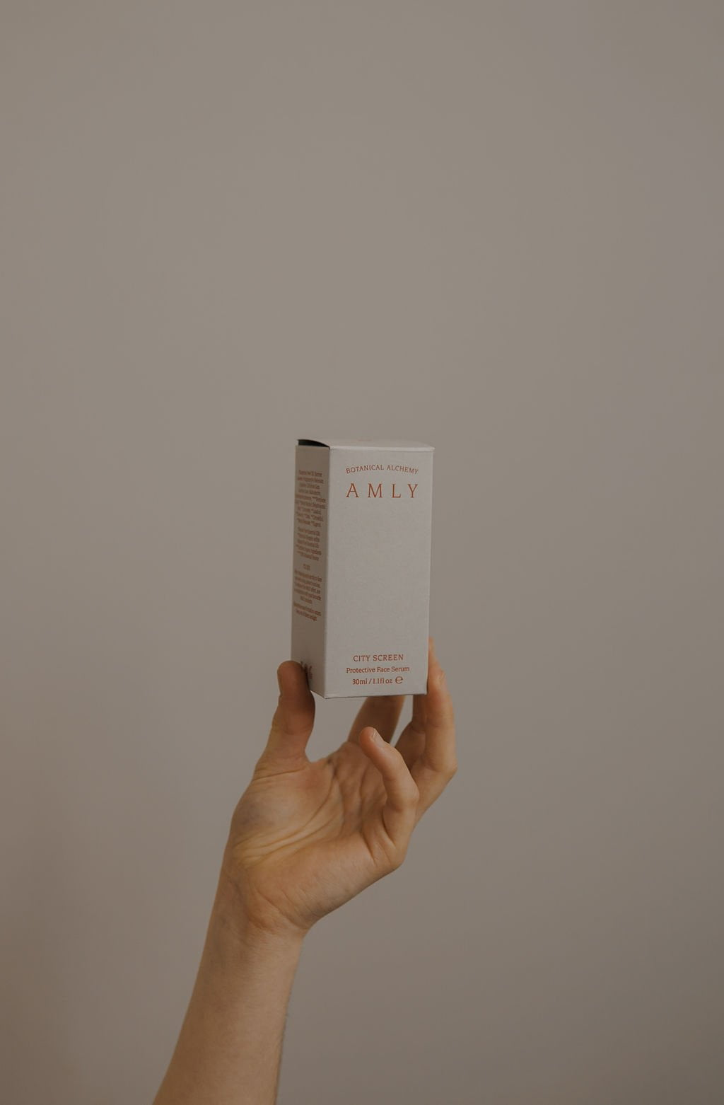 AMLY Botanicals city screen protective face serum box in hand - part of the morning prescription routine