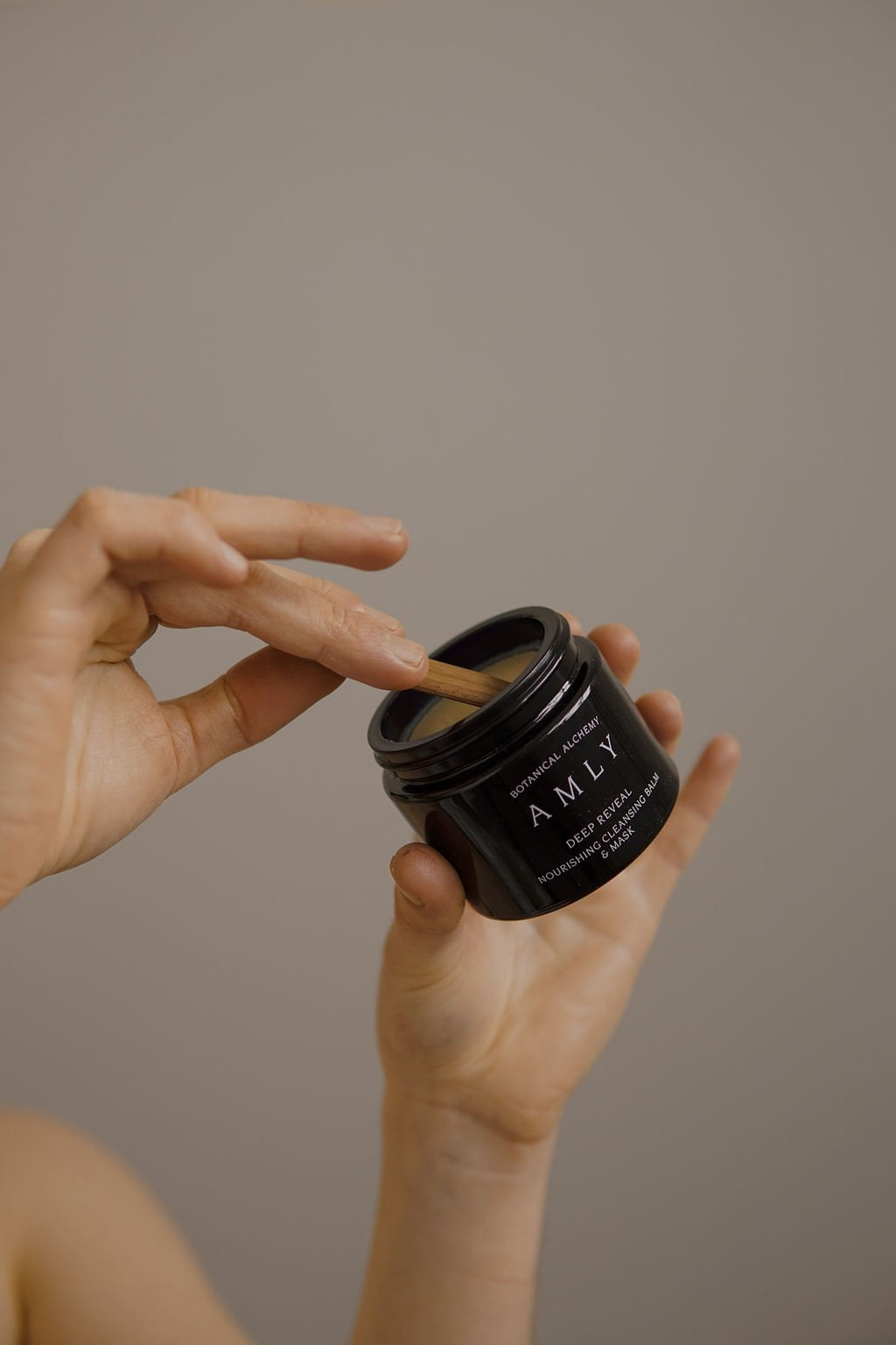 AMLY Botanical Deep Reveal nourishing face mask 100ml in hand, being scooped with spatula
